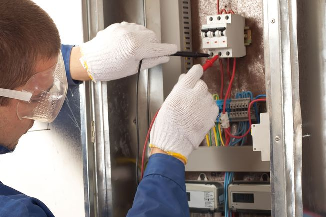 An electrician testing a fuse box